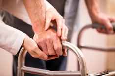 stock-photo-46942550-female-doctor-helps-senior-man-patient-use-walker-holding-hands